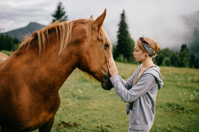 Junge Frau streichelt Pferd auf einer Alm